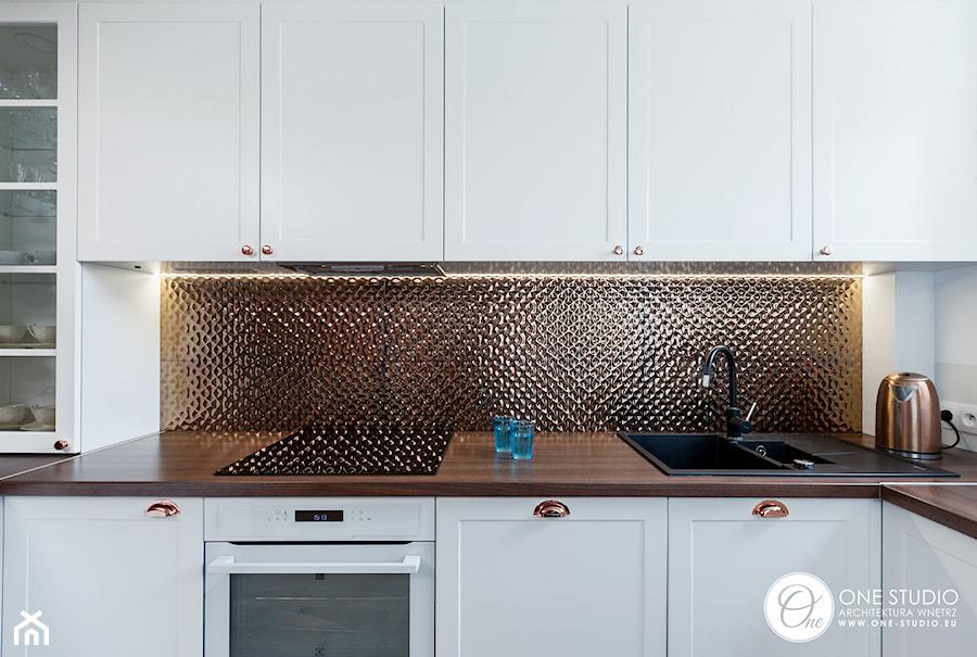 Biała kuchnia z miedzianymi dodatkami - zdjęcie od One Studio