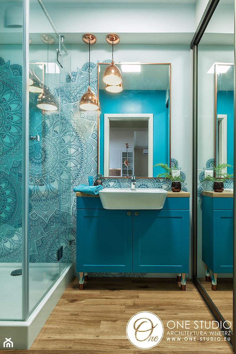 Niebieska łazienka z miedzianymi lampami - zdjęcie od One Studio