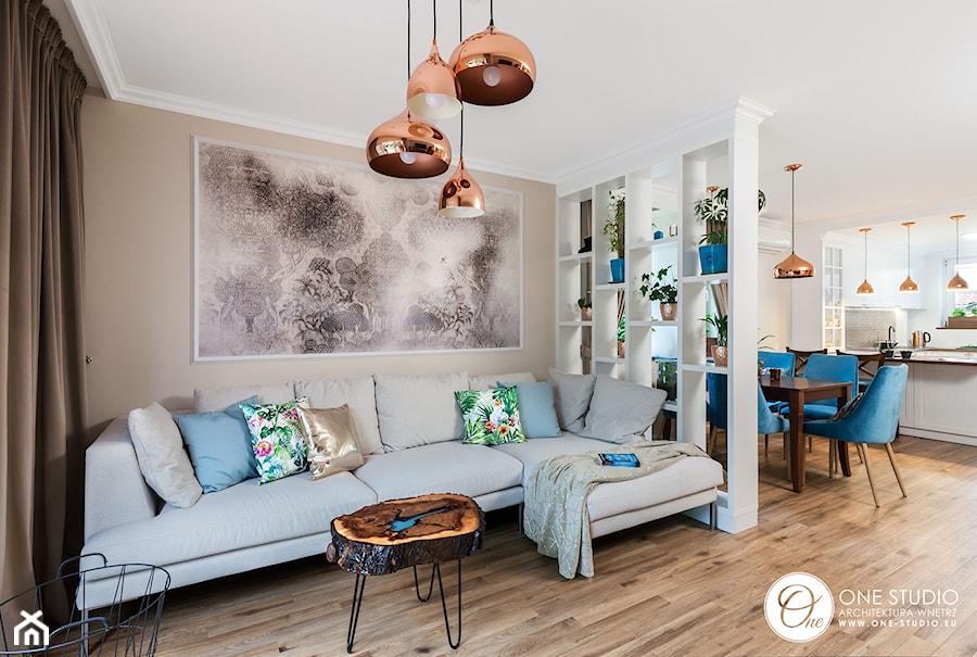 Salon z miedzianymi lampami i stolikiem w postaci plastra pnia zalanego żywicą - zdjęcie od One Studio