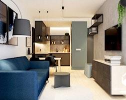 Widok z salonu na kuchnię. Betonowa ściana z TV. Granatowa sofa - zdjęcie od KAROLINA POPIEL - ARCHITEKURA WNĘTRZ - Homebook