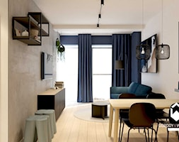Salon z betonową ścianą i granatową sofą - zdjęcie od KAROLINA POPIEL - ARCHITEKURA WNĘTRZ - Homebook