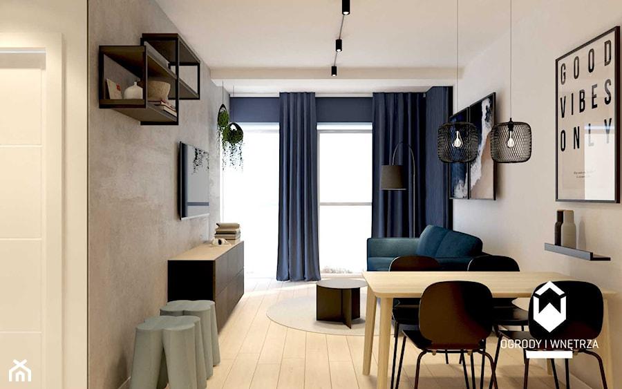 Salon z betonową ścianą i granatową sofą - zdjęcie od KAROLINA POPIEL - ARCHITEKURA WNĘTRZ