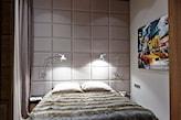 tapicerowana ściana za łóżkiem, metalowe lampy ścienne, połyskująca pościel