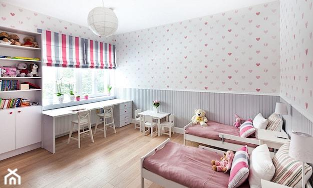 biała ściana w kolorowe serduszka, drewniana podłoga, rolety w kolorowe pionowe paski, białe łóżko