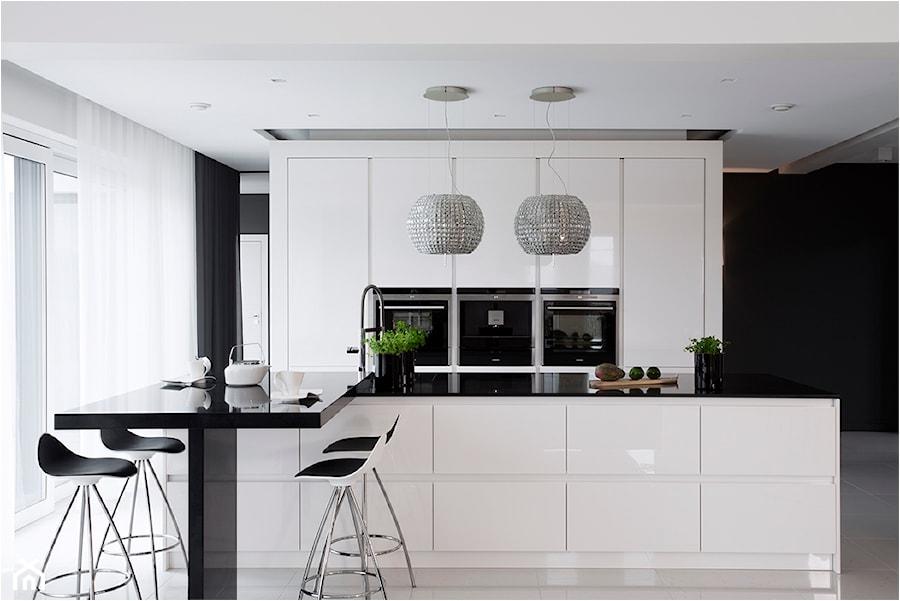 Dom na wysoki połysk - Średnia biała czarna kuchnia dwurzędowa w aneksie z wyspą, styl nowoczesny - zdjęcie od Maria Jachalska