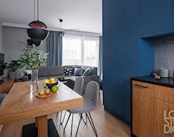 Mieszkanie z niebieskim motywem - Średnia otwarta niebieska szara jadalnia w kuchni w salonie, styl eklektyczny - zdjęcie od Loftstudio