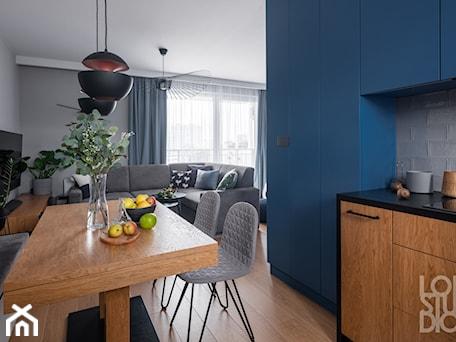 Aranżacje wnętrz - Jadalnia: Mieszkanie z niebieskim motywem - Średnia otwarta niebieska szara jadalnia w kuchni w salonie, sty ... - Loftstudio. Przeglądaj, dodawaj i zapisuj najlepsze zdjęcia, pomysły i inspiracje designerskie. W bazie mamy już prawie milion fotografii!
