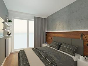 Sypialnia z surową betonową ścianą