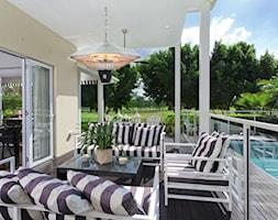 Promienniki - Średni taras z tyłu domu z basenem - zdjęcie od Ogrodolandia