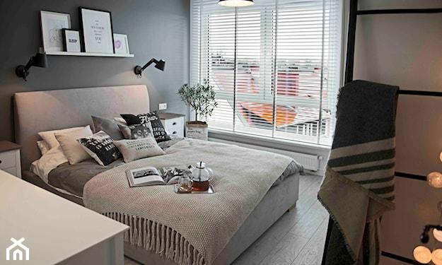 szare łóżko tapicerowane, szara ściana w sypialni