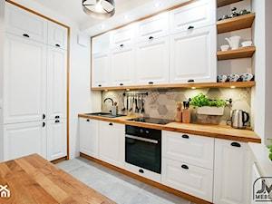 Mała otwarta biała kuchnia dwurzędowa w aneksie z oknem - zdjęcie od hateregs