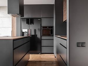 Mieszkanie dla mężczyzny - Duża otwarta czarna kuchnia dwurzędowa z wyspą, styl nowoczesny - zdjęcie od zonaarchitekci