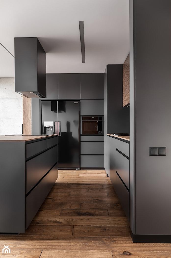 Mieszkanie dla mężczyzny - Duża otwarta czarna kuchnia dwurzędowa z wyspą, styl nowoczesny - zdjęcie od zonaarchitekci - Homebook