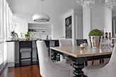 drewniana podłoga, drewniane hokery, stół z czarnymi ozdobnymi nogami