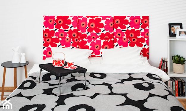 łóżko z zagłówkiem w czerwone kwiaty, biała półka na książki, szara pościel