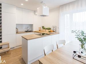 Realizacja projektu wnętrza mieszkania w Krakowie - Mała otwarta biała kuchnia w kształcie litery u w aneksie z wyspą, styl nowoczesny - zdjęcie od TIKA DESIGN