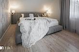 sypialnia na poddaszu z dużym szarym tapicerowanym łóżkiem