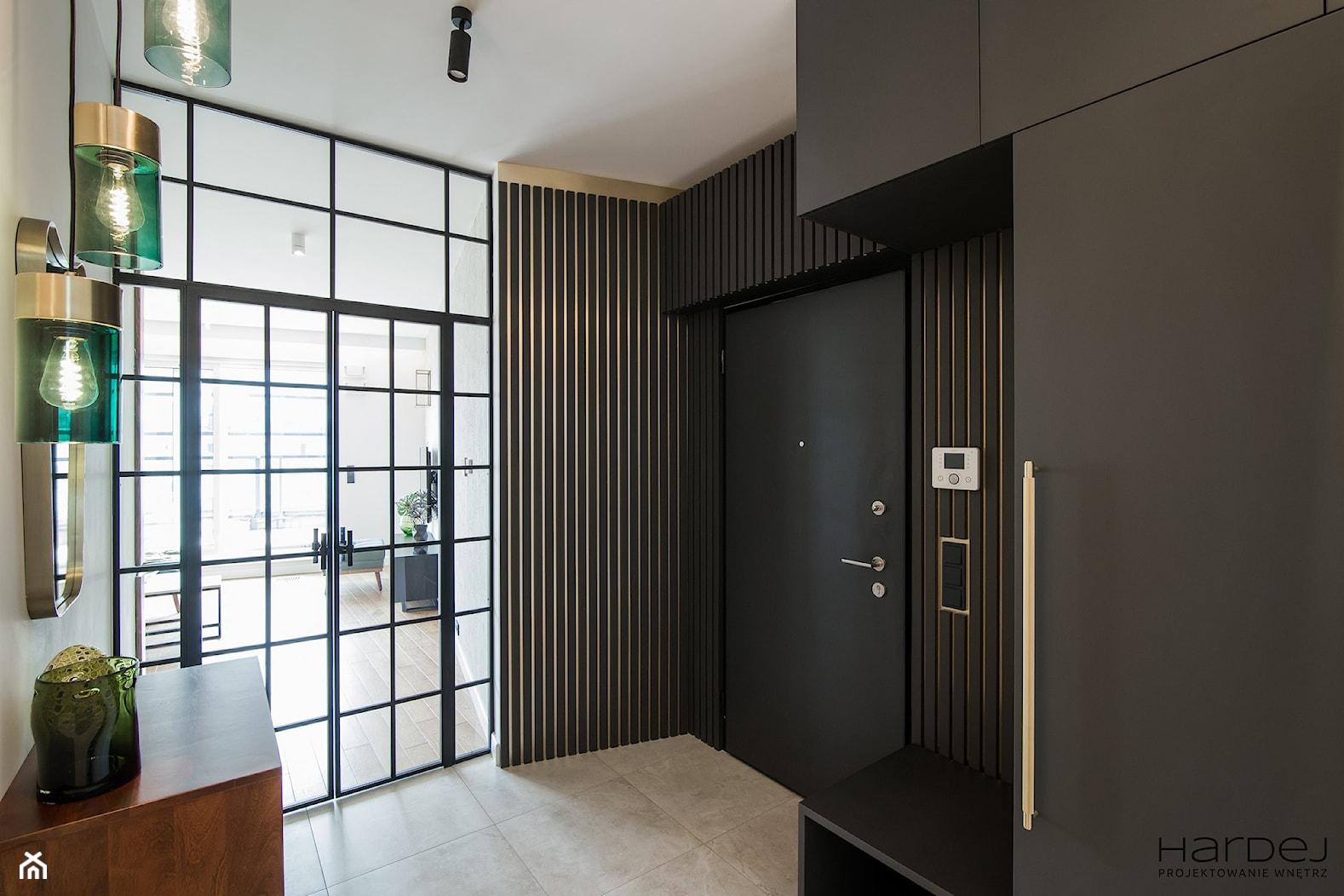 Hol z ciemną szafą, pawlaczem i ciemnymi szczeblami na ścianie - zdjęcie od Monika Hardej Architekt - Homebook
