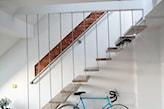 niebieski rower, białe ściany, cegła naturalna, drewniane schody