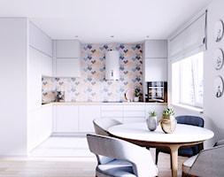 Biała kuchnia otwarta na salon z pastelową ścianą - zdjęcie od OkapyKuchenne.pl - Homebook