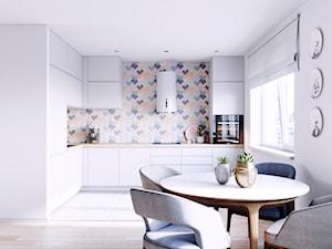 Biała kuchnia z pastelowymi płytkami typu mozaika i białym okapem w kształcie tuby