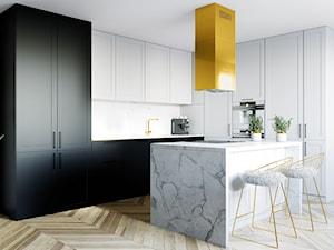 Biało-czarna kuchnia ze złotymi elementami i marmurową wyspą