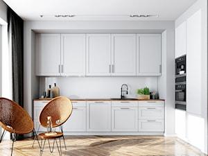 Minimalistyczna biała kuchnia z drewnianym blatem o okapem do zabudowy