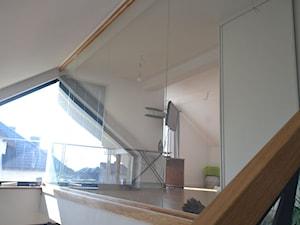 Nowoczesne schody dywanowe z ażurową ścianą i szklaną balustradą