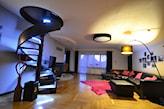 spiralne metalowe schody, drewniana podłoga, narożnik z czarnej skóry, czerwone poduszki