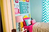 niebieskie ściany, różowa pościel, żółte łóżko, lampka z różowym abażurem