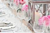 szklane kieliszki, różowe kwiaty, metalowy lampion, biała świeczka