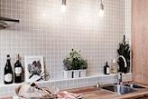 beżowa mozaika na ścianie w kuchni, drewniany blat kuchenny, białe doniczki ze świeżymi ziołami