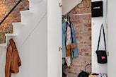 ceglana ściana, pleciony kosz, garderoba pod schodami