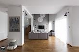 szara sofa, drewniana podłoga, biała lampa wisząca kula, szara ściana