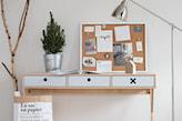 drewniane biurko, srebrna lampka i tablica korkowa