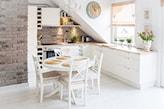 kuchnia na poddaszu w stylu skandynawskim, biały okrągły stół, szara cegła, beżowa roleta rzymska
