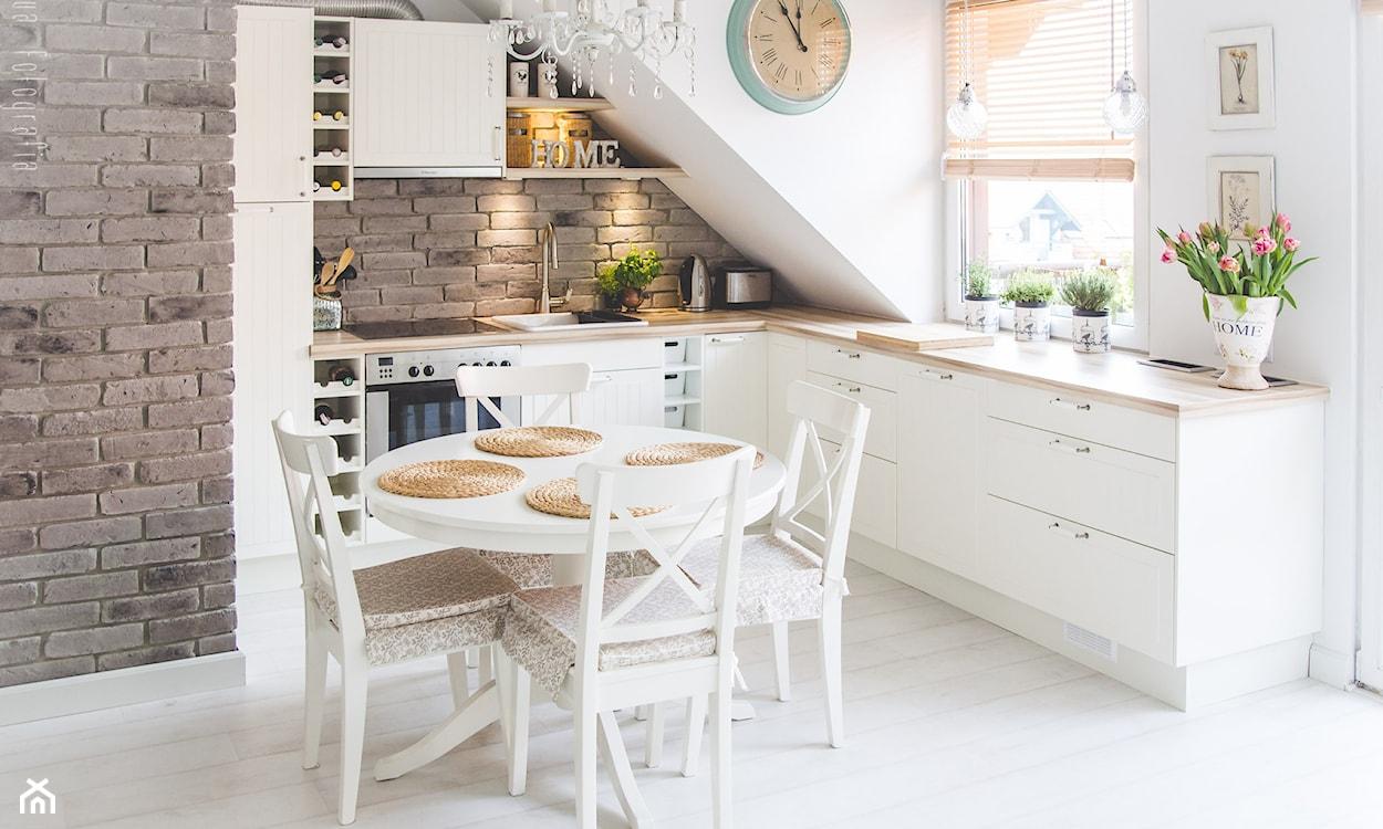 biała kuchnia na poddaszu z drewnianymi akcentami
