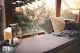 duży parapet, szara narzuta, szklany wazon, białe poduszki