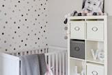 ściana w kolorowe kropki w pokoju dziecka, białe łóżeczko dziecięce, biała komoda, cotton balls