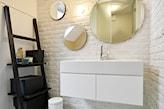 biała cegła w łazience, okrągłe lustro bez ramy, białe szafki łazienkowe