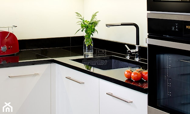 blat kuchenny z czarnego marmuru, białe szafki kuchenne