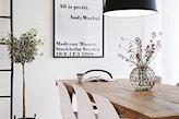 drewniany stół, białe krzesła, czarna lampa wisząca, biały obraz