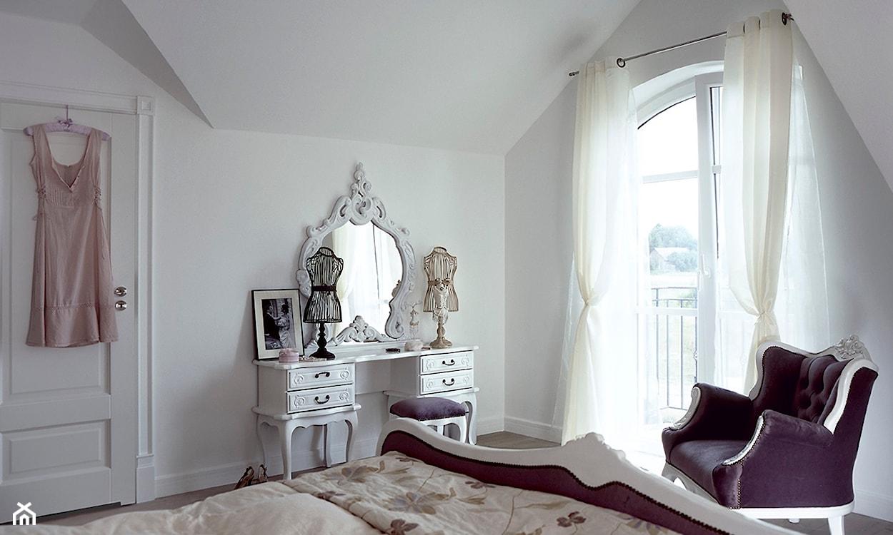 biała toaletka z lustrem w ozdobnej ramie, białe ściany, fioletowy fotel, białe ściany