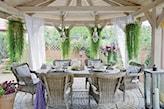 drewniana altana, wiklinowe krzesła, białe zasłony