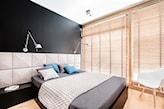 szare łóżko z szarym zagłówkiem, drewniane rolety, niebieskie poduszki, biała lampa ścienna, drewniane żaluzje