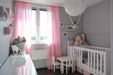 różowe zasłony, szare ściany w pokoju dziecka, biały stolik dziecięcy, białe łóżeczko dziecięce