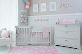 różowy dywanik w białe kropki, biała lamperia, biała komoda, białe łóżeczko dziecięce z różowym materacem
