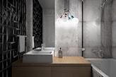 mała łazienka, czarne kafelki w łazience, wanna z parawanem, płytki betonowe na ścianie