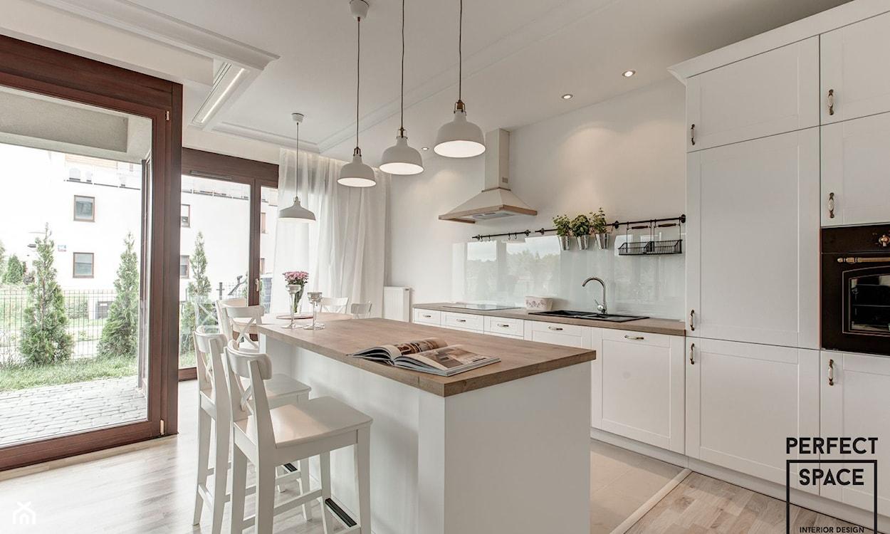 białe meble kuchenne z drewnianym blatem, białe lampy wiszące, białe hokery