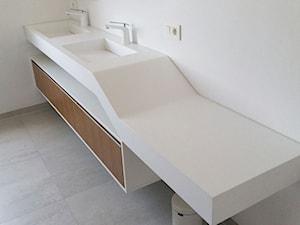 Podwójna geometryczna umywalka z blatem i fornirowaną szafką.